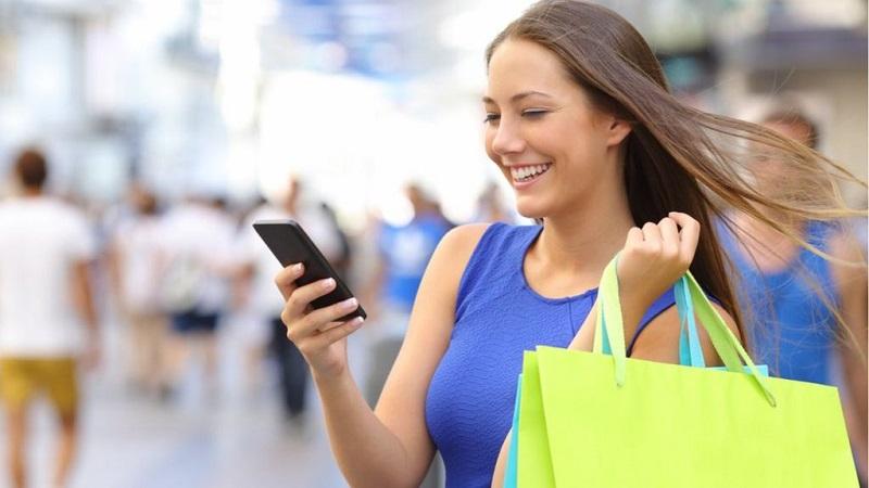 Mulher fazendo compras e usando o celular em Pretória