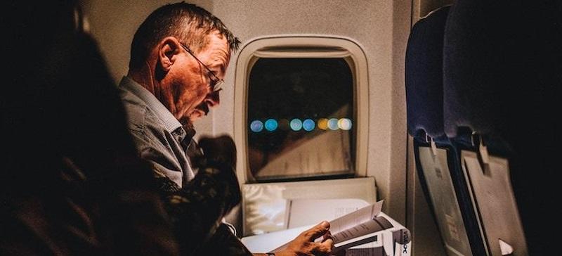Homem lendo em um voo para a Cidade do Cabo