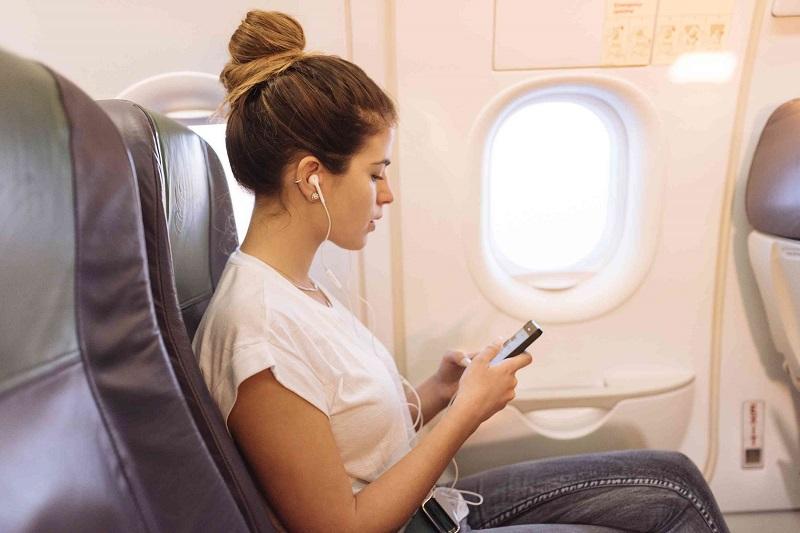Pessoa usando o celular no avião