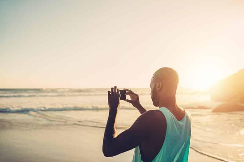 Homem tirando foto em praia da África do Sul